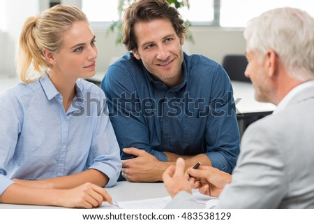 Businessman explaining loan policy to young couple. Happy couple discussing with a financial agent their new investment. Financial consultant presents bank investments to a smiling woman and her man.