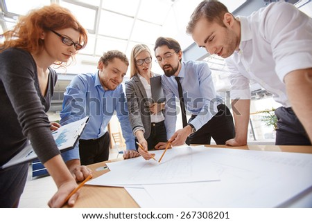 Businessman explaining project to his colleagues at meeting - stock photo