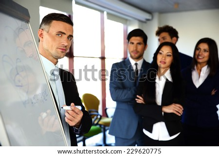 Businessman explaining something on the flipboard to his colleagues