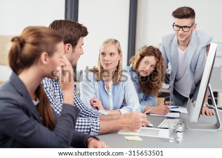 Businessman Explaining Something to his Colleagues While having a Meeting at his Desk. - stock photo