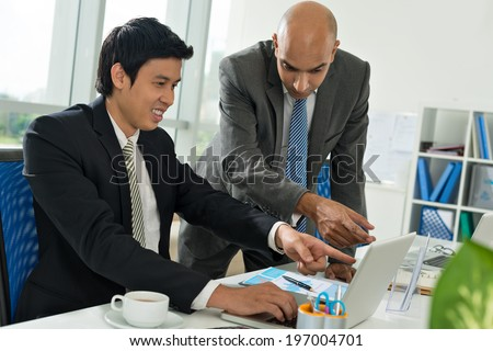 Businessman explaining something to his Vietnamese colleague - stock photo