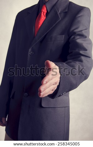 businessman extending hand to shake - stock photo