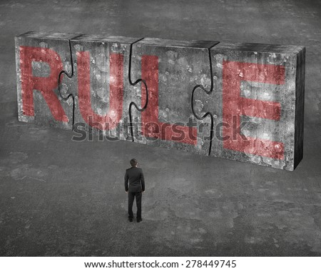 Businessman facing red rule word on four huge concrete puzzles connected together, on gray cement floor background - stock photo