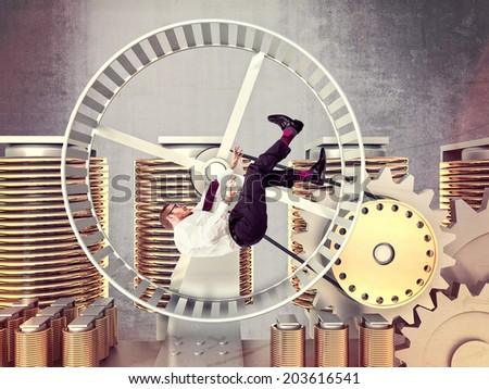 businessman fall in a huge hamster wheel - stock photo