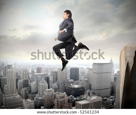 Businessman falling from a skyscraper over a city - stock photo