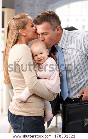 Businessman father arriving home from work, wife and little baby daughter greeting him with kiss. - stock photo