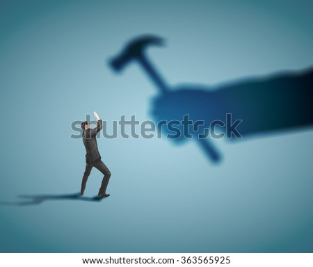 businessman fears shadow hammer blow - stock photo