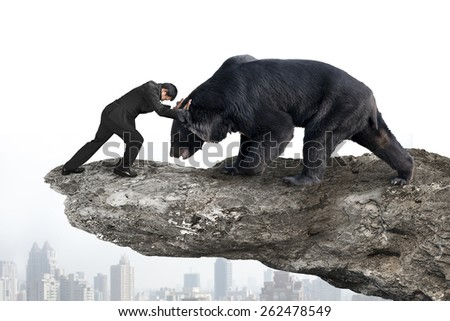 Businessman fighting against black bear on cliff with sky cityscape background - stock photo