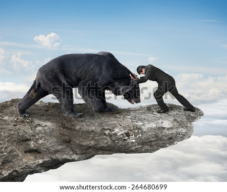 Businessman fighting against black bear on cliff with sky cloudscape background - stock photo