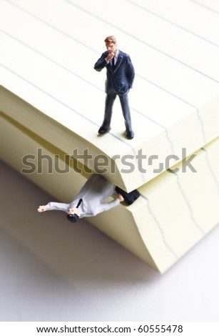Businessman figurine standing on a notepad - stock photo