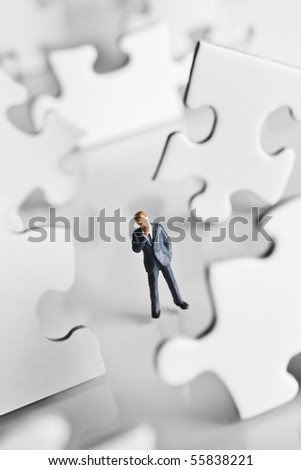 Businessman figurine surrounded by puzzle pieces