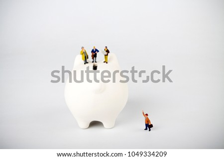 Businessman figurines on a piggybank. Money, business and expectation concept.