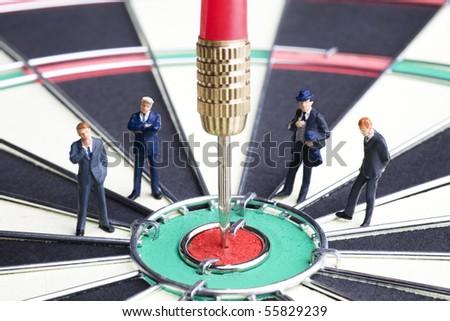 Businessman figurines placed on a dartboard - stock photo