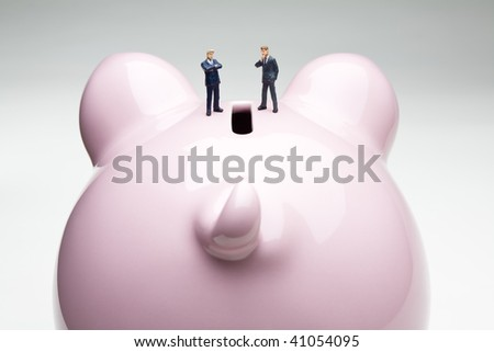 Businessman figurines placed on a piggy bank - stock photo