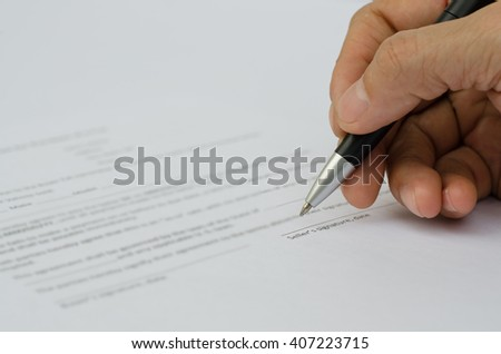Businessman filling a contract for purchase of car with black pen. - stock photo