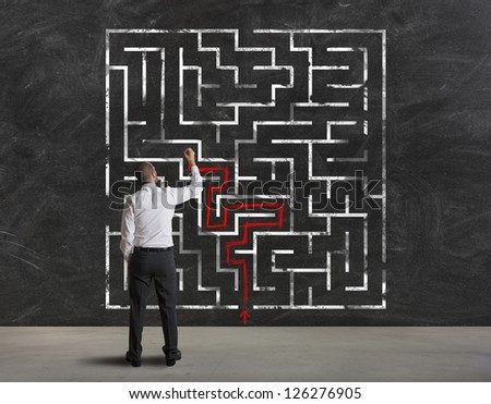 Businessman finding the solution of a maze - stock photo