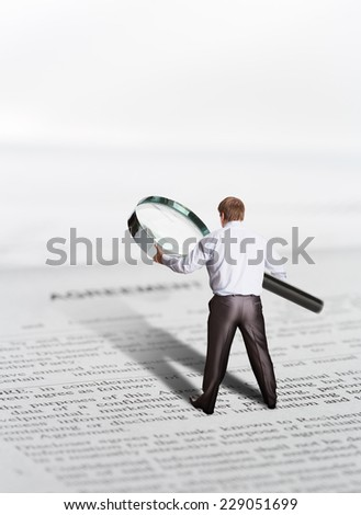 Businessman finds something with loupe - stock photo