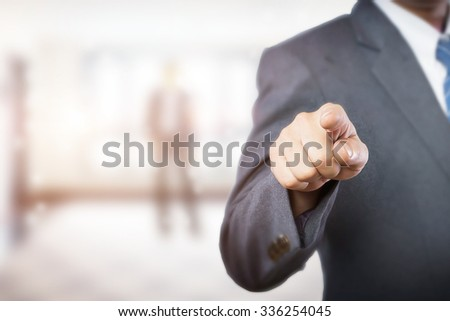 Businessman finger pointing on blank virtual screen at office background in morning light.  - stock photo