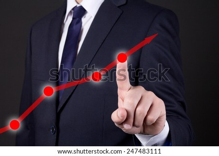 businessman finger touching red rising arrow over dark background - stock photo