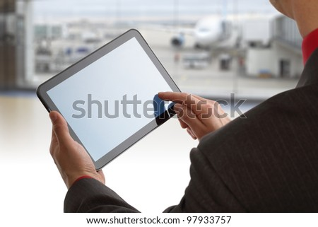 Businessman finger touching screen of a digital tablet at the departure gate of an airport