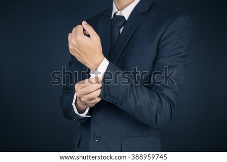 Businessman Fixing Cuff links his Suit