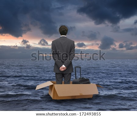 businessman floating at sea in a cardboard box