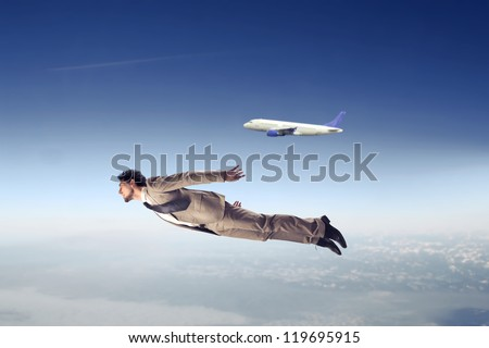 Businessman flying near an airliner - stock photo