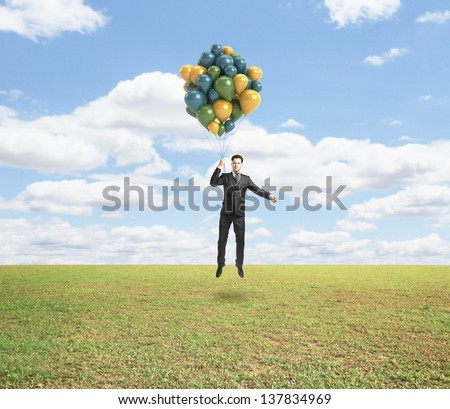 businessman flying with air balloons over field - stock photo