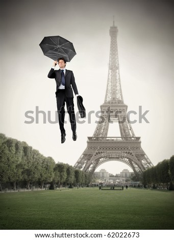 Businessman flying with an umbrella over a park with Eiffel Tower on the background - stock photo