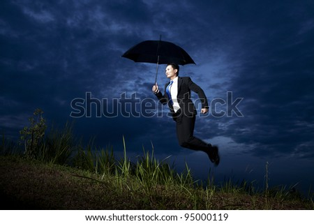 Businessman flying with umbrella on a cloudy day