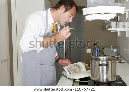 Businessman following the instructions in a cooking book to cook food at home, tasting it with a wooden spoon. - stock photo