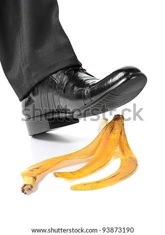 Businessman foot about to slip and fall on a banana peel on white background - stock photo