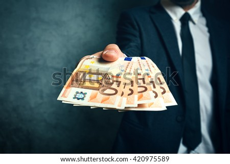 Businessman from bank offering money loan in euro banknotes, selective focus. - stock photo