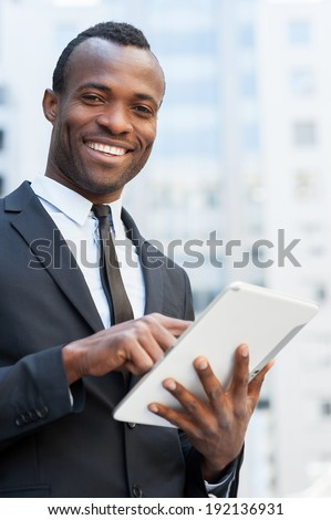 Businessman from digital age. Cheerful young African man in formal wear working on digital tablet and smiling while standing outdoors - stock photo