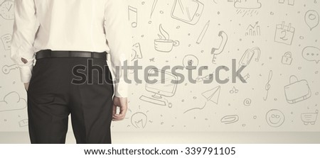 Businessman from the back in front of an social media icon wall  - stock photo