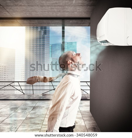 Businessman frozen by the air conditioner power - stock photo