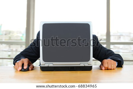 Businessman frustrated with technology with his head down on his laptop. Man is hidden behind computer only his hands and arms are visible. Horizontal format in modern office in front of window. - stock photo
