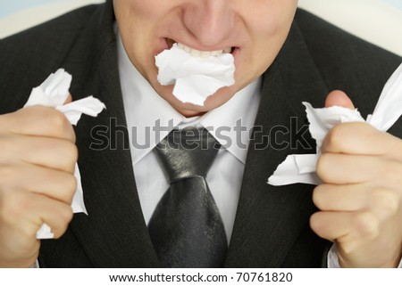 Businessman furiously tearing paper with his teeth and hands - stock photo