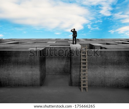 Businessman gazing on top of concrete Maze wall with wooden ladder and blue sky - stock photo