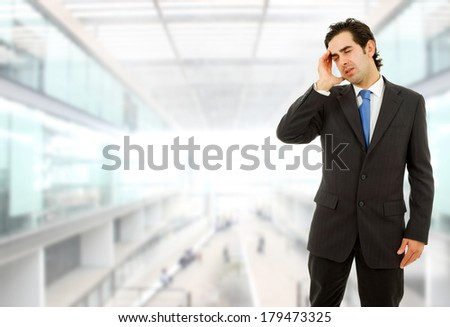 Businessman gestures with a headache, at the office - stock photo