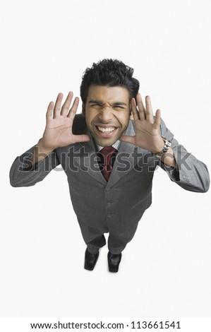 Businessman gesturing and making a funny face - stock photo