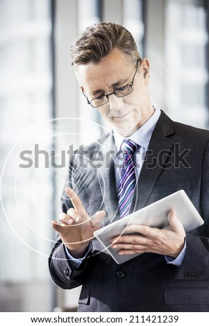 Businessman gesturing while using digital tablet in office - stock photo