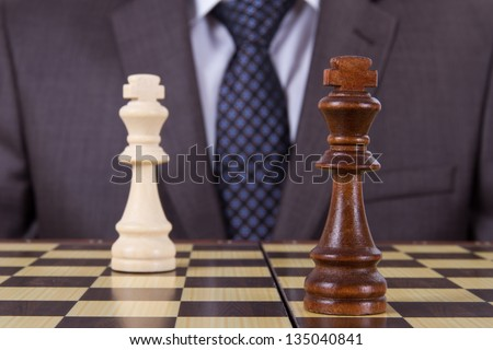 Businessman get drawn on chess game, two kings on chess board. - stock photo