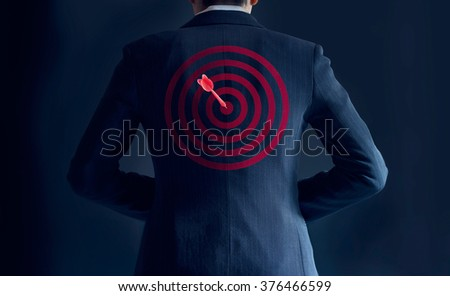 businessman get success with red arrow on target at the back of his suit on dark background, business concept - stock photo