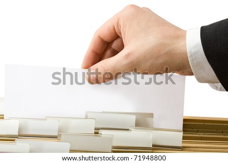Businessman gets paper from row of office folders - stock photo