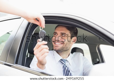 Businessman getting his new car key in his car - stock photo