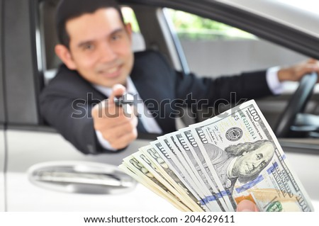 Businessman giving a car key exchanging with money - car ( auto) pawn concept - stock photo