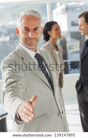 Businessman giving a handshake with colleagues behind discussing together - stock photo