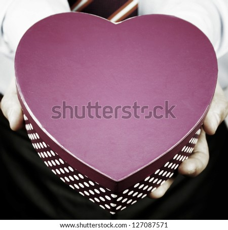 Businessman giving a heart gift - stock photo