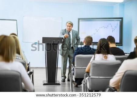 Businessman giving a presentation on flipchart. Teamwork concept - stock photo